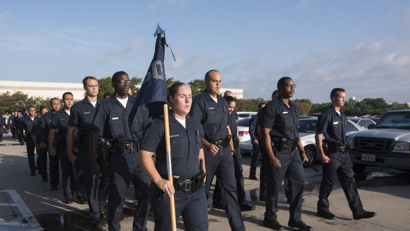 Dallas Police Department recruits march through morning formation at the Dallas Police Academy.