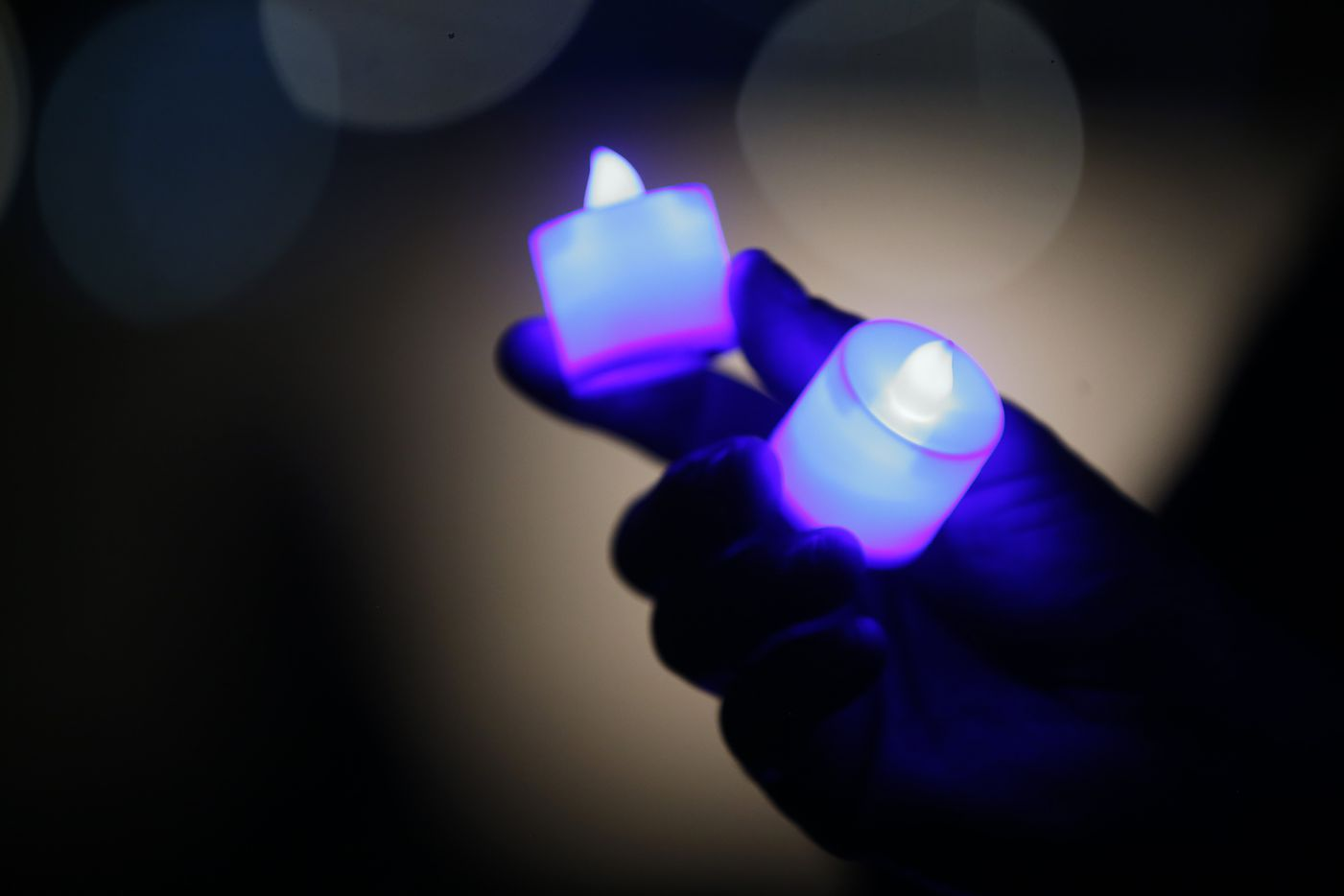 A person holds two blue lights during the Tribute 7/7 closing ceremony at Dallas Police Memorial in Dallas, Friday, July 7, 2017.