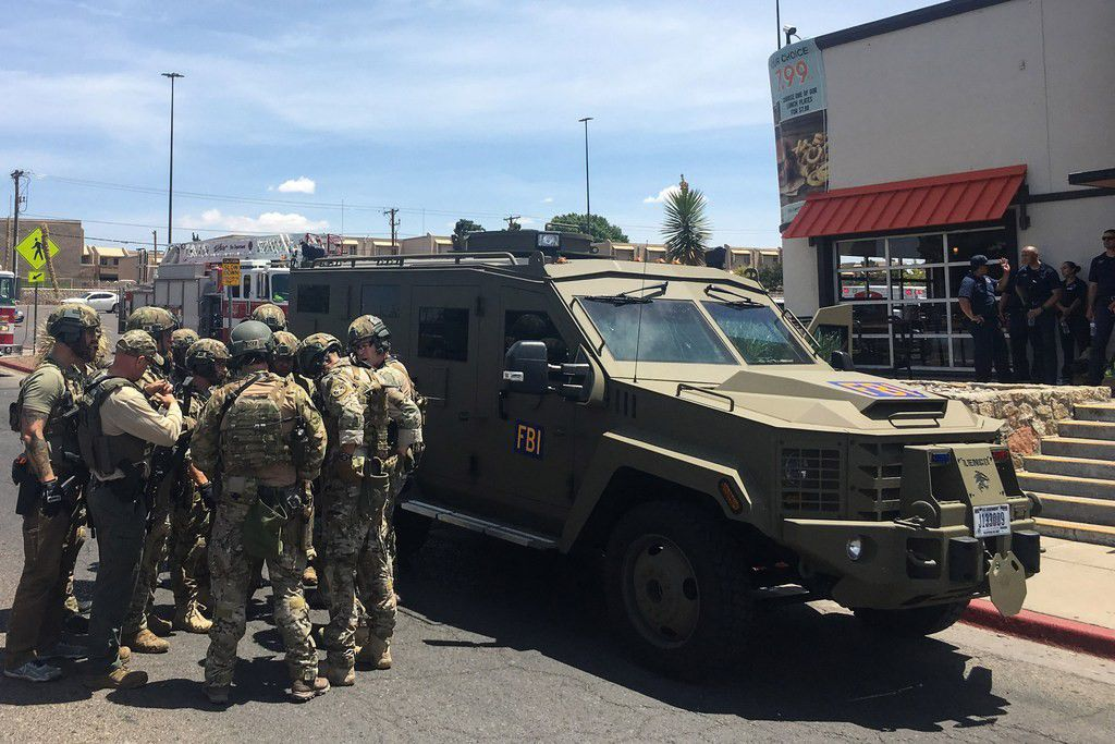 """Armed Policemen gather next to an FBI armoured vehicle next to the Cielo Vista Mall as an active shooter situation is going inside the Mall in El Paso on August 03, 2019. - Police said there may be more than one suspect involved in an active shooter situation Saturday in El Paso, Texas. City police said on Twitter they had received """"multi reports of multipe shooters."""" There was no immediate word on casualties."""