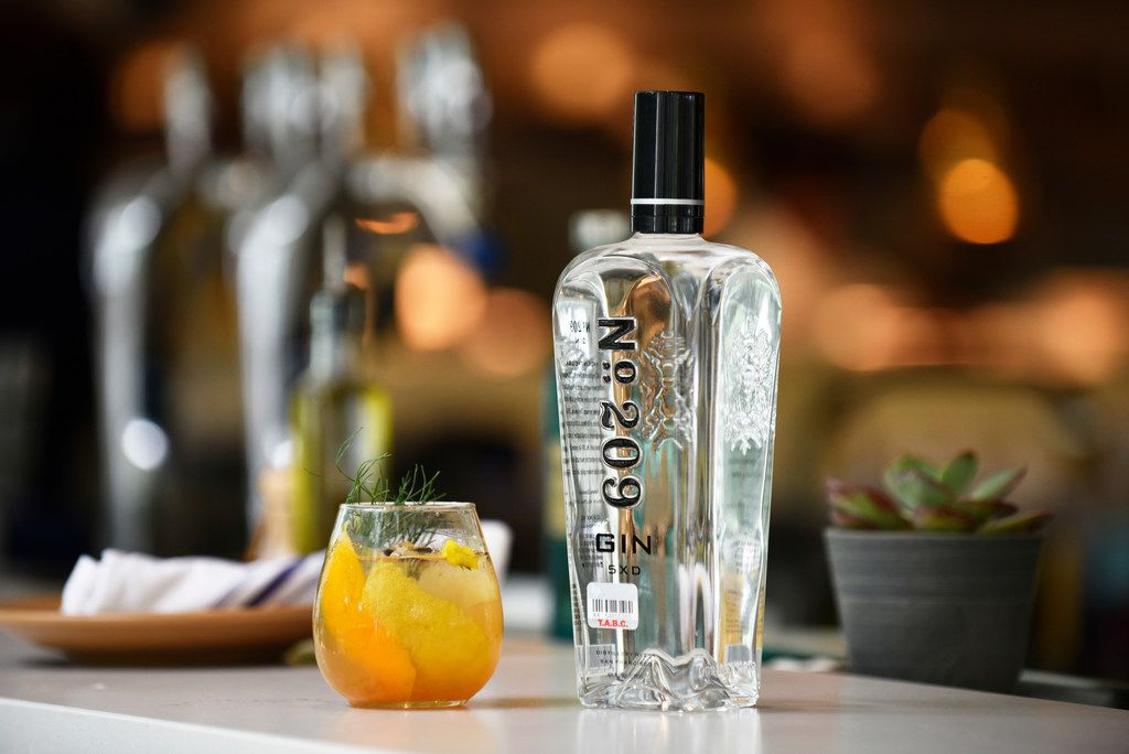 A bottle of No. 209 gin and a gin and tonic drink made with Italicus di Rosolio di Bergamotto, fennel fronds and orange peel from Sachet in Dallas.