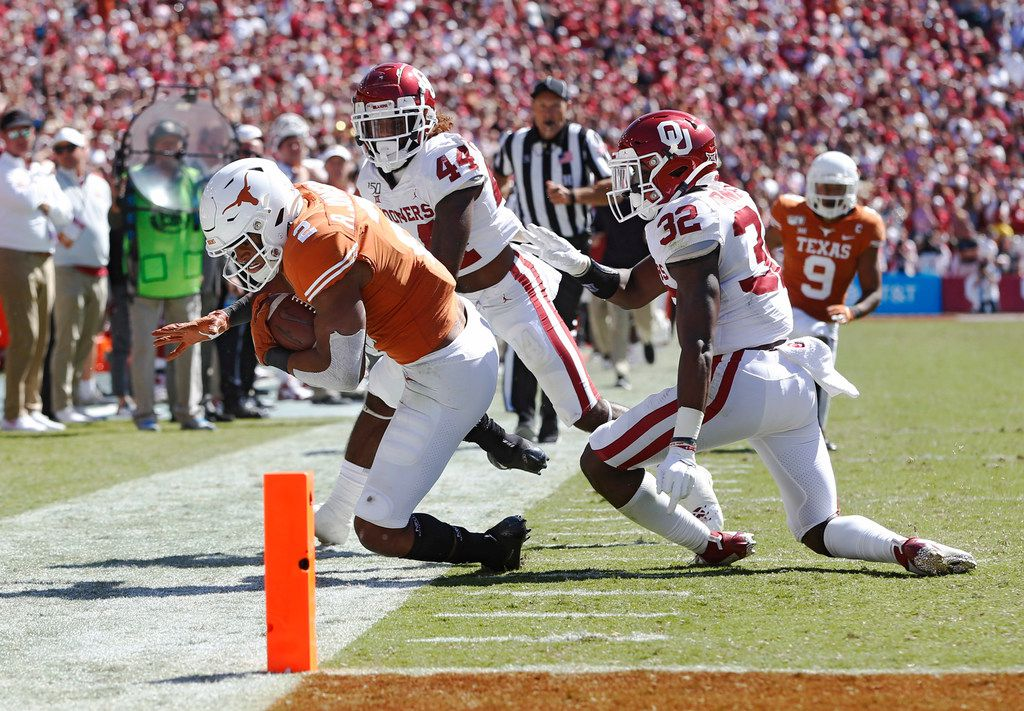 FILE - Texas running back Roschon Johnson (2) is pushed out of bounds by Oklahoma defensive backs Brendan Radley-Hiles (44) and Delarrin Turner-Yell (32) during the second half of the Red River Showdown at the Cotton Bowl in Dallas on Saturday, Oct. 12, 2019.
