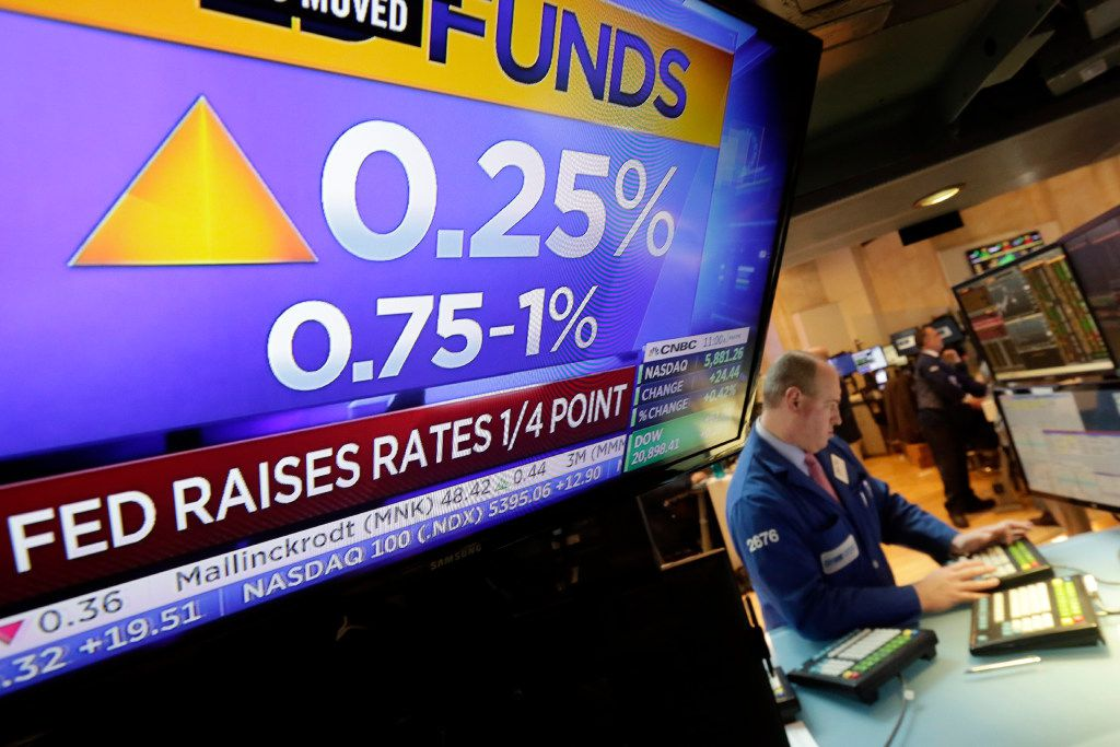 Specialist Edward Loggie works at his post as a television screen on the floor of the New York Stock Exchange shows the decision of the Federal Reserve, Wednesday, March 15, 2017. The Fed's key short-term rate is rising by a quarter-point to a still-low range of 0.75 percent to 1 percent. (AP Photo/Richard Drew)