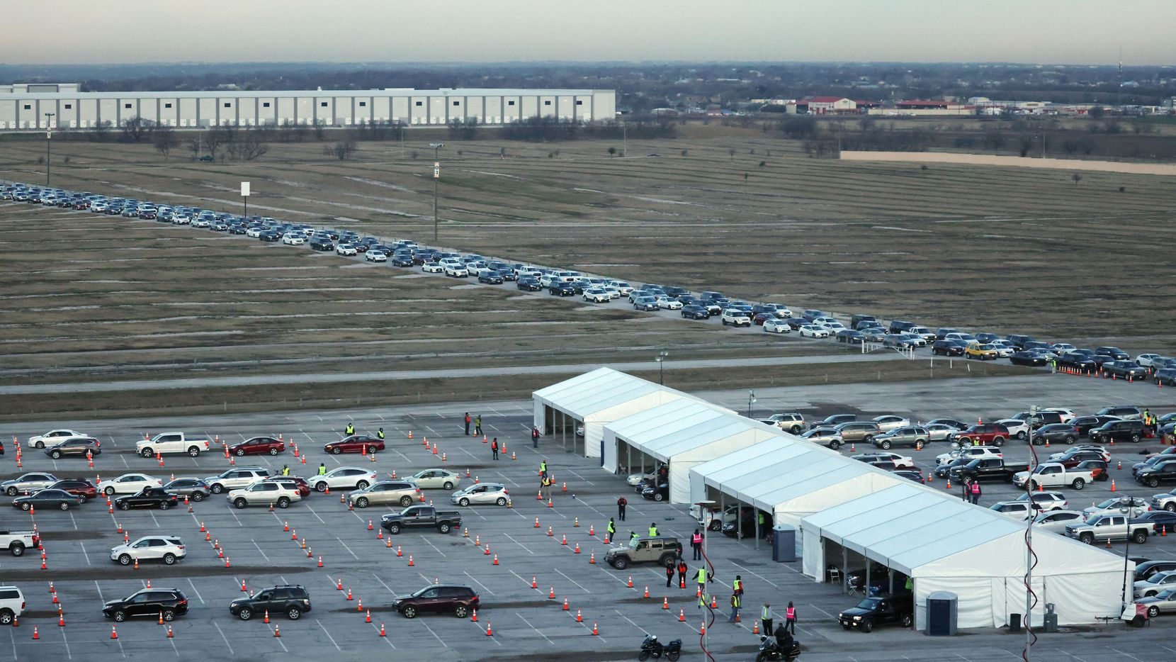 Vehicles make their way through multiple stations at a COVID-19 drive-through vaccination clinic at Texas Motor Speedway. Denton County has recently begun offering free bus rides for anyone who is heading to the speedway to receive a vaccine.
