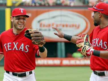 Texas Rangers second baseman Ian Kinsler (5) and  shortstop Elvis Andrus (1) are all smiles after turning a double play in the fifth inning during the Toronto Blue Jays vs. the Texas Rangers major league baseball game at Rangers Ballpark in Arlington on Saturday, June 15, 2013.  (Louis DeLuca/Dallas Morning News)
