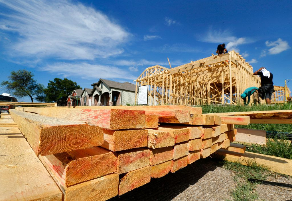 Stacked lumber sits on the sidewalk as construction workers frame out a new home along Malcolm X Blvd in South Dallas, Monday, July 10, 2017. (Tom Fox/The Dallas Morning News)