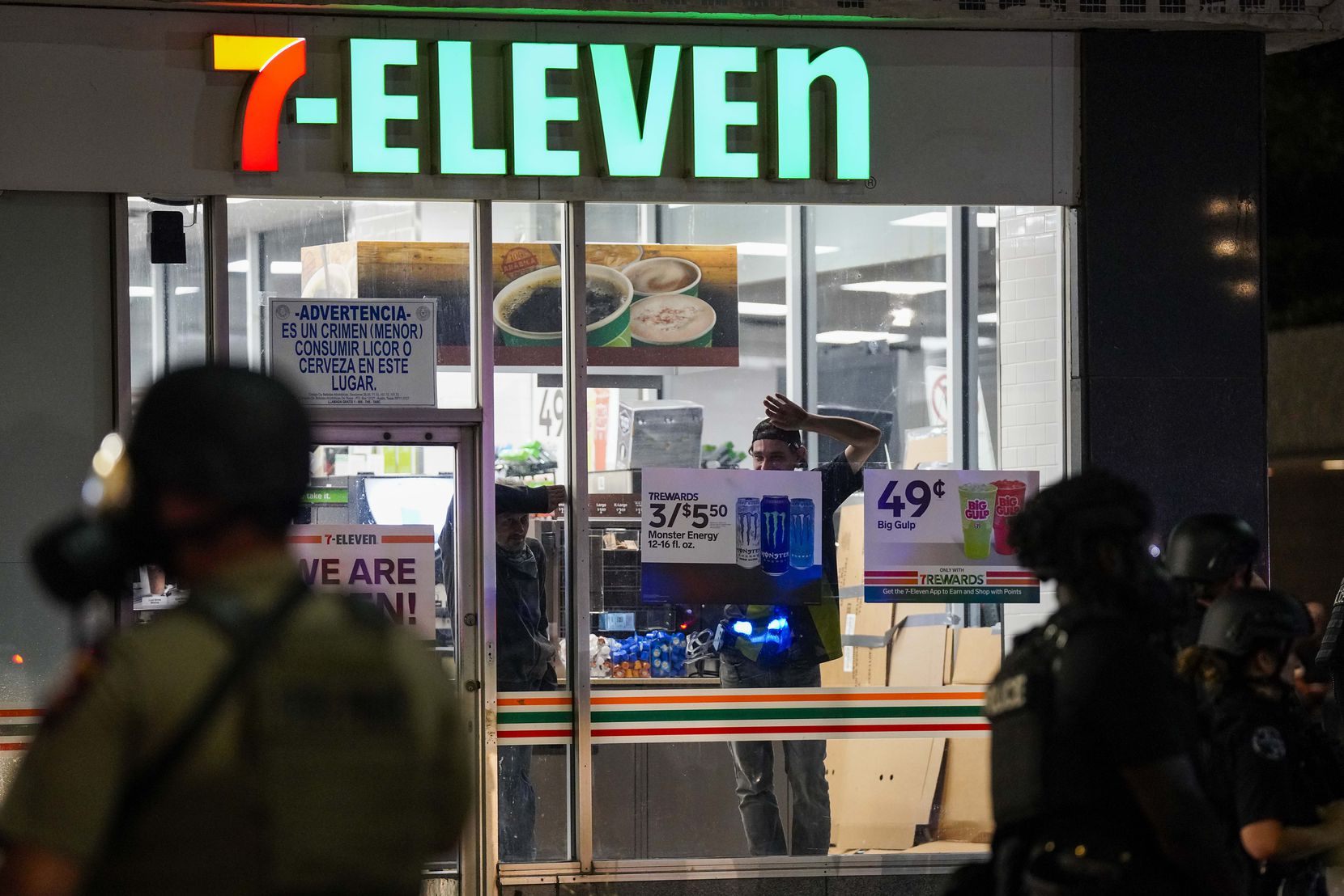 Men look out the windows of the 7-11 store on Elm Street at Ervay as Dallas police and  Texas Department of Public Safety troopers work to clear groups of people from downtown streets following a protest against police brutality in the early morning hours of Saturday, May 30, 2020, in Dallas.