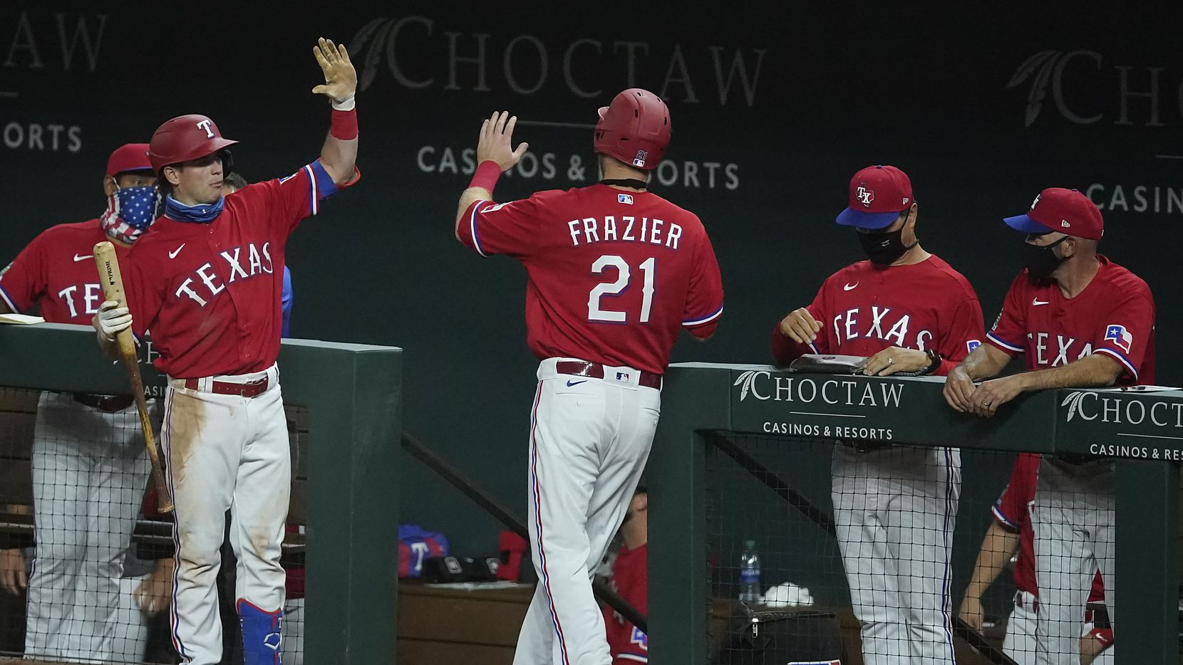 Texas Rangers third baseman Todd Frazier gets a socially distanced high five from outfielder Nick Solak after scoring on a bases-loaded walk by Los Angeles Angels starting pitcher Griffin Canning during the fourth inning at Globe Life Field on Friday, Aug. 7, 2020.