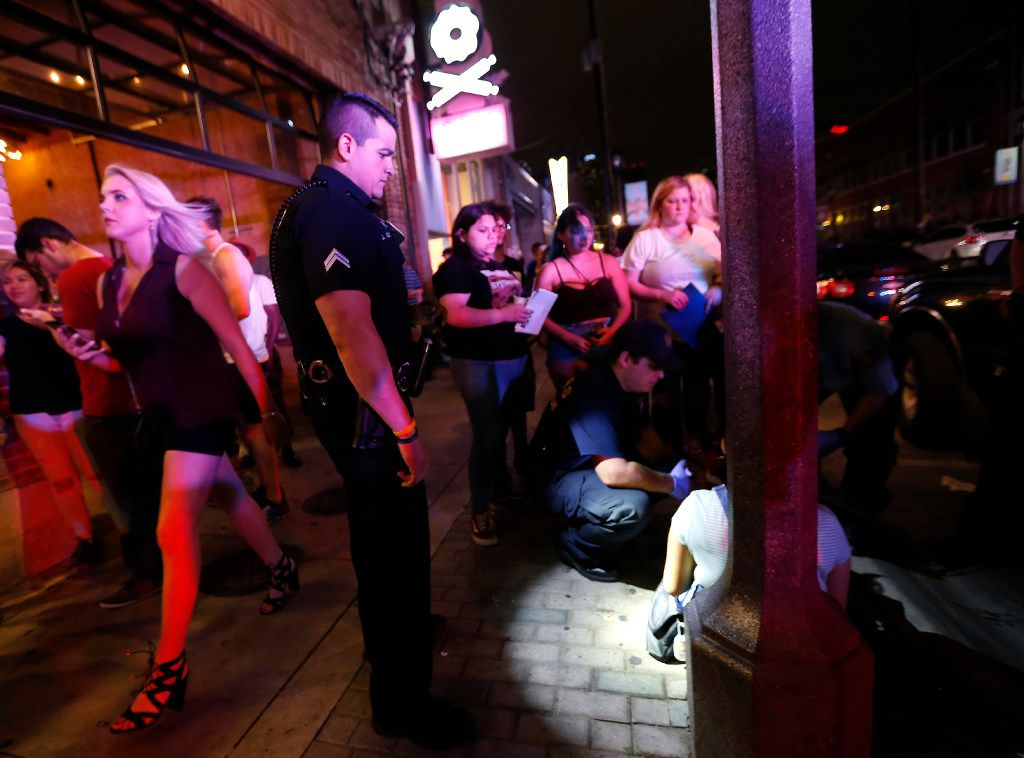 Police and paramedics on the job along Deep Ellum's row of bars, blocks from where a rape victim was abducted last month.