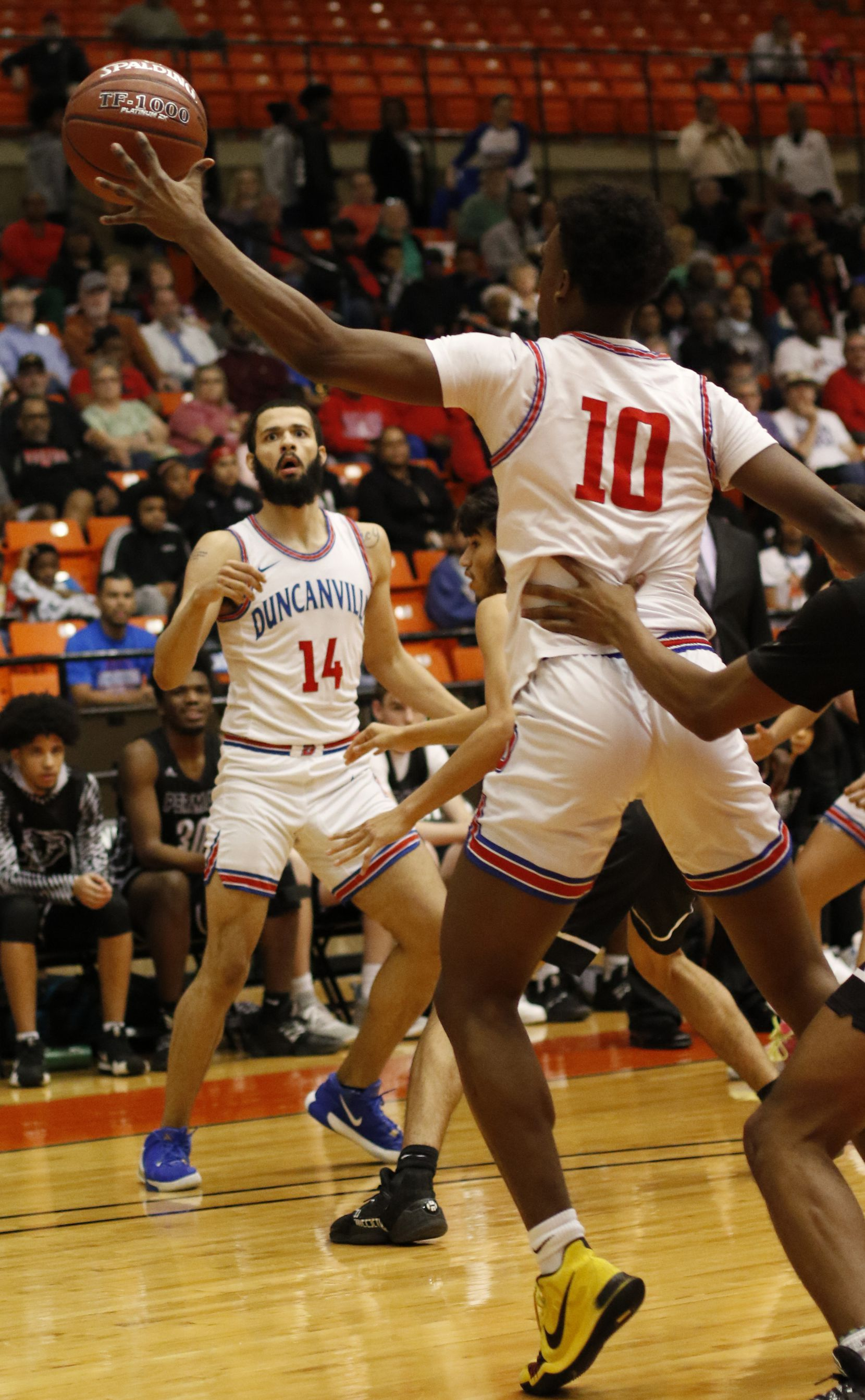 Duncanville forward Robert Banks (14) watches his pass reach its destination as guard Damon Nicholas (10) pulls it in during first half action against Odessa Permian. The two teams played in the Class 6A Region 1 championship boys basketball playoff game at Wilkerson-Greines Activity Center in Fort Worth on March 7, 2020.