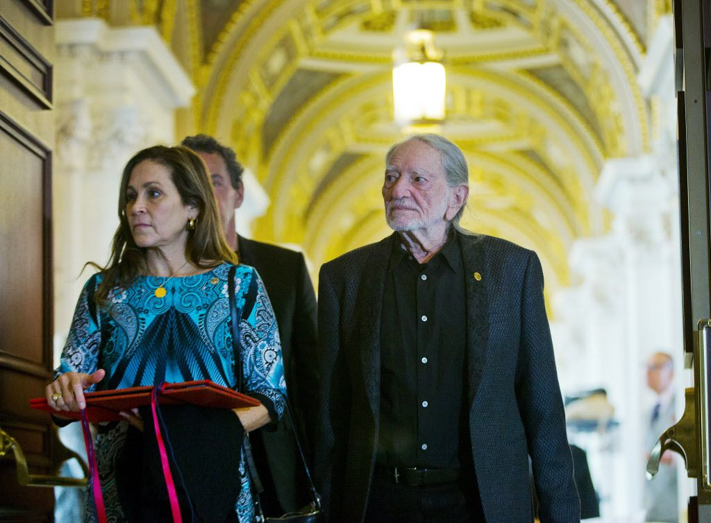 Musician Willie Nelson, right, and his wife Annie D'Angelo, left, walk the hallways of the Library of Congress, during their tour, Tuesday, Nov. 17, 2015 in Washington.
