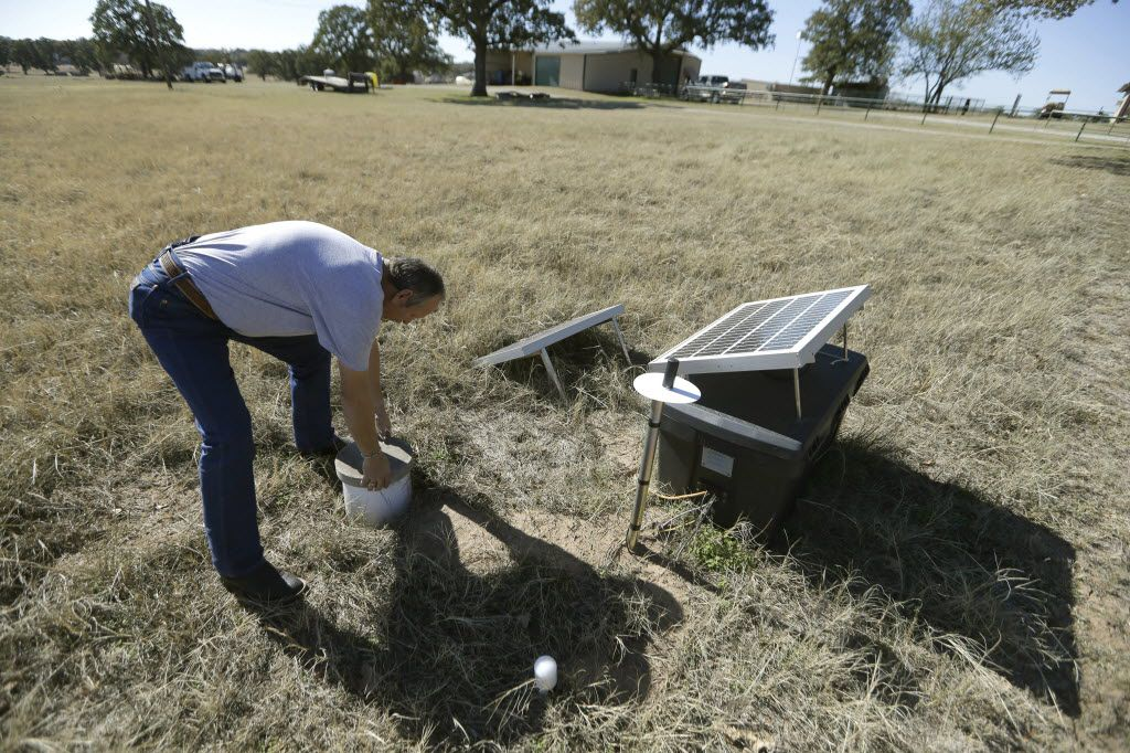 Scott Passmore, director of public works, checks on a solar-powered seismic monitor that records earthquakes in the area around Reno, Texas. (2014 File Photo/The Associated Press)