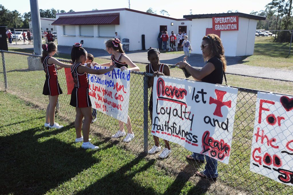 In this 2012 file photo, the cheerleaders of Kountze Middle School display faith-based  signs at the middle school football game held at Kountze High School.