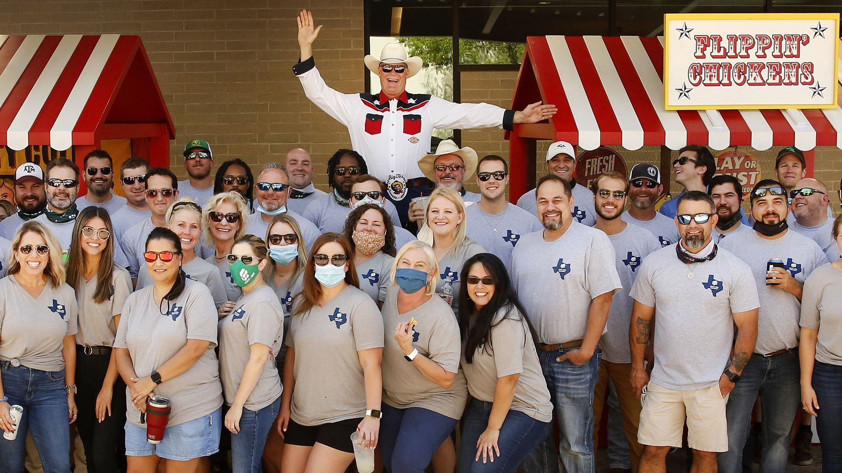 Dressed and posing as Big Tex, Scott + Reid General Contractors founder and president Brad Reid (center) joined his employees for a photo during the company's (Un)Fair Day in Addison on Sept. 25. Usually on opening day of the State Fair of Texas, the employees get the day off to spend at the fair. Instead they brought a fair to their company parking lot.