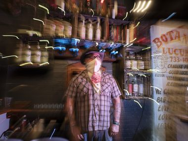 Co-owner Shad Kvetko photographed with a slow camera shutter behind the bar at the Spirits Room inside Las Almas Rotas in Dallas