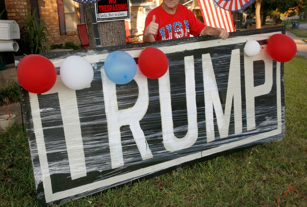 Jerry Tarter gives a thumbs up as he poses behind a big Donald Trump sign he made with plywood and put in his front yard in Garland a couple weeks before the election.