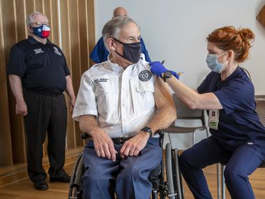 Registered nurse April Burge give Gov. Greg Abbott his first dose of the Pfizer-BioNtech COVID-19 vaccine at the Ascension Seton Medical Center on Dec. 22, 2020. Commissioner Dr. John William Hellerstedt  of the Texas Department of State Health Services far left and Registered nurse Toby Hatton looks on.