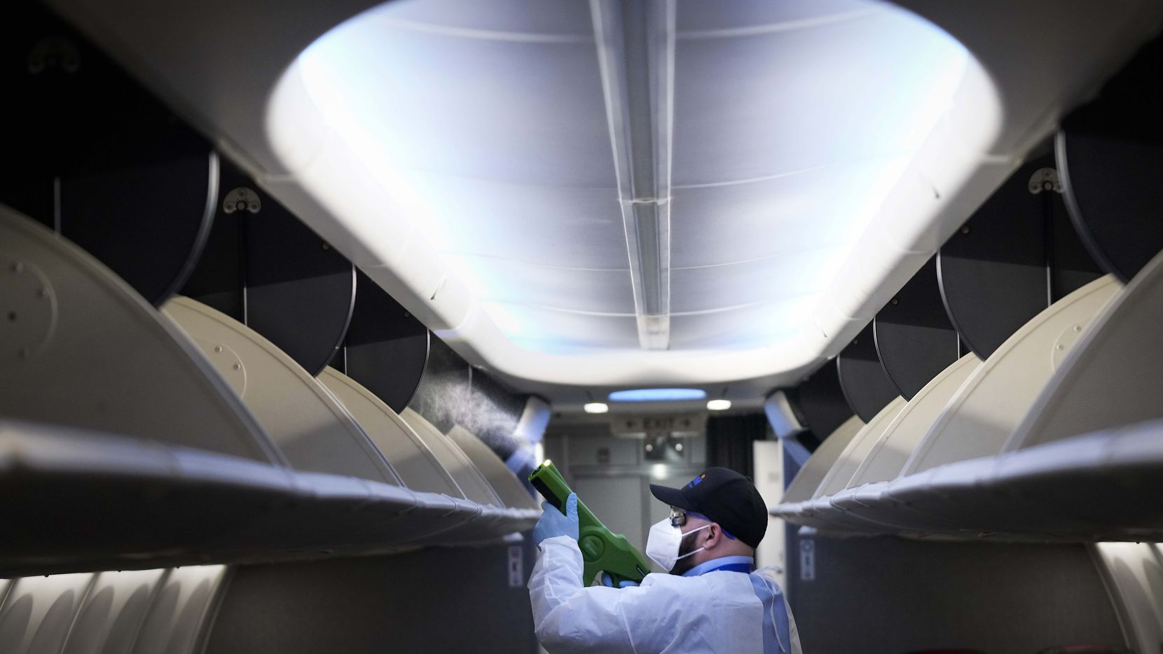 Jamie Shatinsky of ABM Aviation uses a handheld electrostatic disinfectant sprayer while disinfecting an American Airlines aircraft at Dallas Fort Worth (DFW) International Airport Terminal A on Tuesday, June 30, 2020, in Dallas. (Smiley N. Pool/The Dallas Morning News)