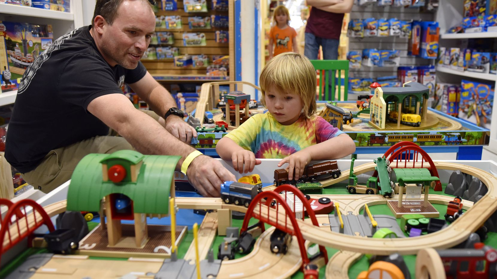 Ned Frost, 43, and son Julian Frost, 4, play with a train set while shopping inside The Toy Maven store at the Preston Royal Shopping Center in Dallas, Friday afternoon, March 16, 2018.