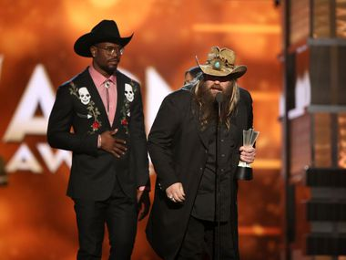 """Chris Stapleton accepts the award for song of the year for """"Nobody to Blame"""" at the 51st annual Academy of Country Music Awards. Presenter Von Miller -- from Dallas! -- looks on."""