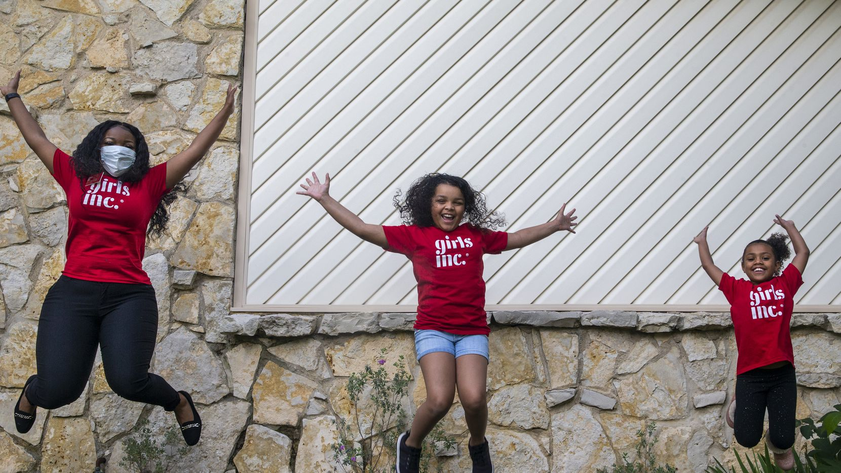 Natalie Cain (left), program facilitator for Girls Inc. of Metropolitan Dallas, enjoys a celebratory moment with two children who she mentors, sisters Aubrey Mendez (center), 10, and Destini King, 7, at the girls' home in North Dallas. Cain says she connects with the girls several times each week.