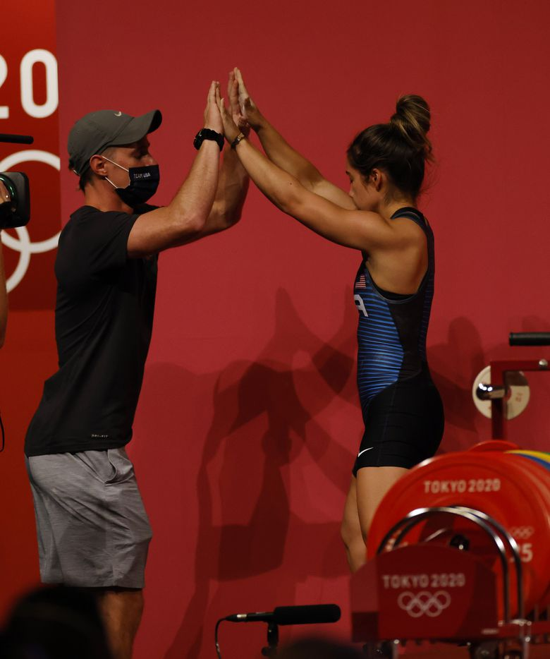 USA's Jourdan Delacruz celebrates with coach Spencer Arnold after completing the first attempt in the snatch round during the women's 49 kg weightlifting final during the postponed 2020 Tokyo Olympics at Tokyo International Forum on Saturday, July 24, 2021, in Tokyo, Japan. (Vernon Bryant/The Dallas Morning News)