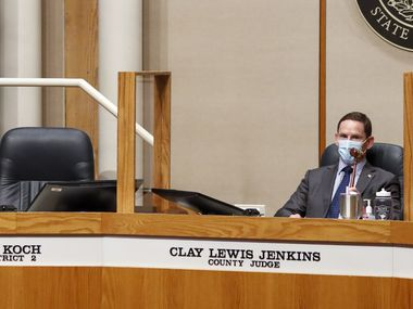 Dallas County Judge Clay Jenkins bangs a gavel next to the empty seat of Dallas County Commissioner J.J. Koch during a Dallas County Commissioners Court meeting on Tuesday, Aug. 3, 2021, in Dallas. Koch was escorted from the meeting for refusing to wear a mask. (Elias Valverde II/The Dallas Morning News)