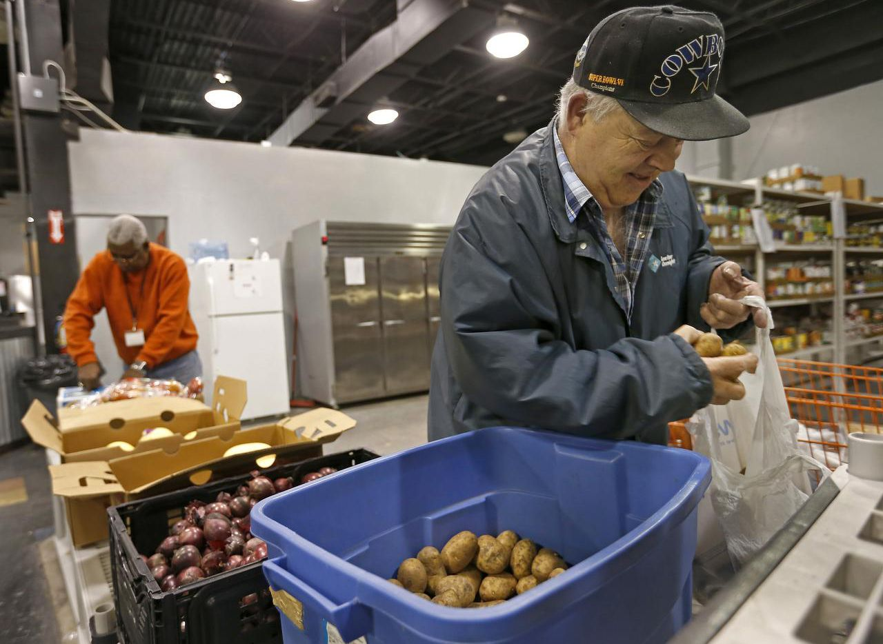 Herb West bags up potatoes as volunteer Robert Gilliam (background) unpacks groceries at the food pantry at Sharing Life Community Outreach in Mesquite.