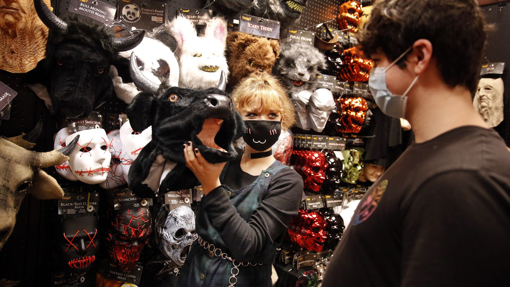 Leah Staten mimics a cow mooing as she and her friend Joel Fernandez look through masks at Spirit Halloween, a pop-up store on Coit Road in Dallas.