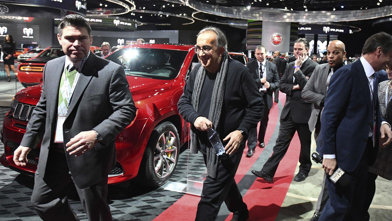Sergio Marchionne, director general de Fiat Chrysler (centro) camina en el North American International Auto Show en Detroit.(AP)