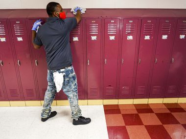 Custodian Jadarius Crawford disinfects lockers at the Paul L. Dunbar Learning Center in Dallas.