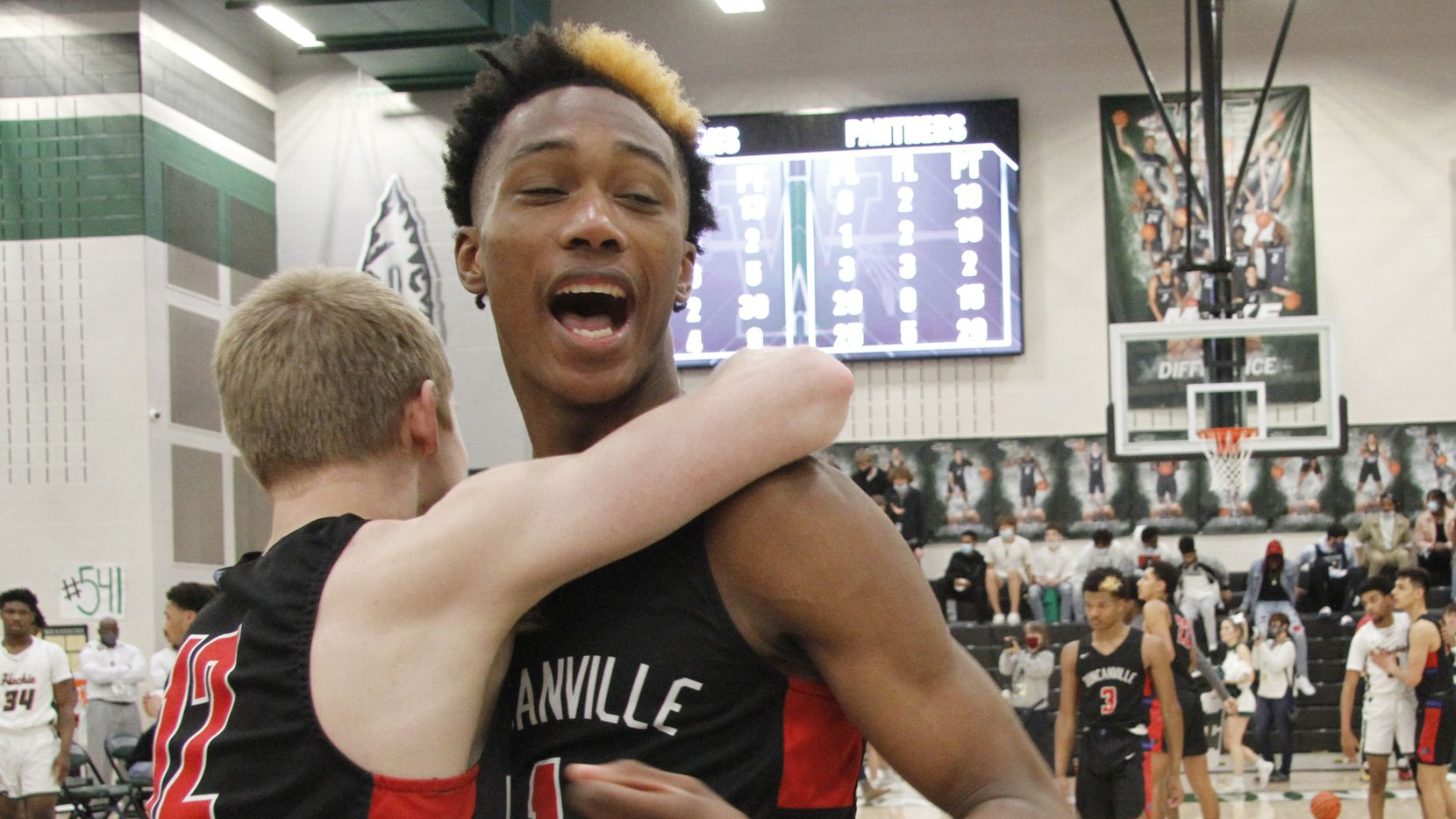 Duncanville's Ronald Holland (right) and teammate Jackson Prince celebrate after a 70-65 victory over Waxahachie in last season's Class 6A Region II final on March 5, 2021. (Steve Hamm/Special Contributor)