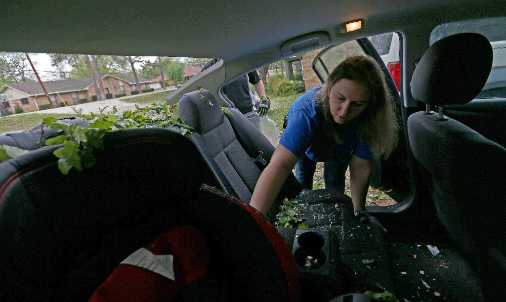 Tara Shadoan takes her belongings before the insurance company tows her car damaged by last night's hailstorm in Highland Village, Texas, Monday, March 27, 2017. (Jae S. Lee/The Dallas Morning News)