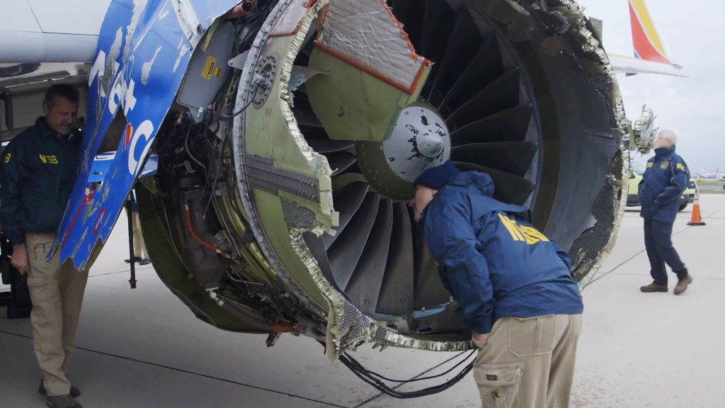 In this Tuesday, April 17, 2018 frame from video, a National Transportation Safety Board investigator examines damage to the engine of the Southwest Airlines plane that made an emergency landing at Philadelphia International Airport in Philadelphia. (NTSB via AP)