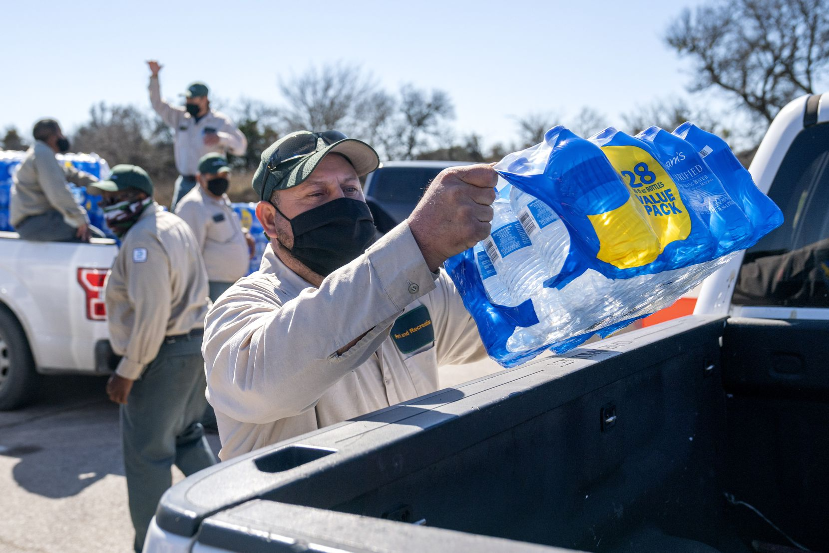 Jesus Muñiz loaded a case of bottled water in a pickup, Monday, February 22, 2021, during a water distribution organized by the City of Dallas Office of Emergency Management in response to snow storm Uri at Kiest Park Recreation Center in Oak Cliff.