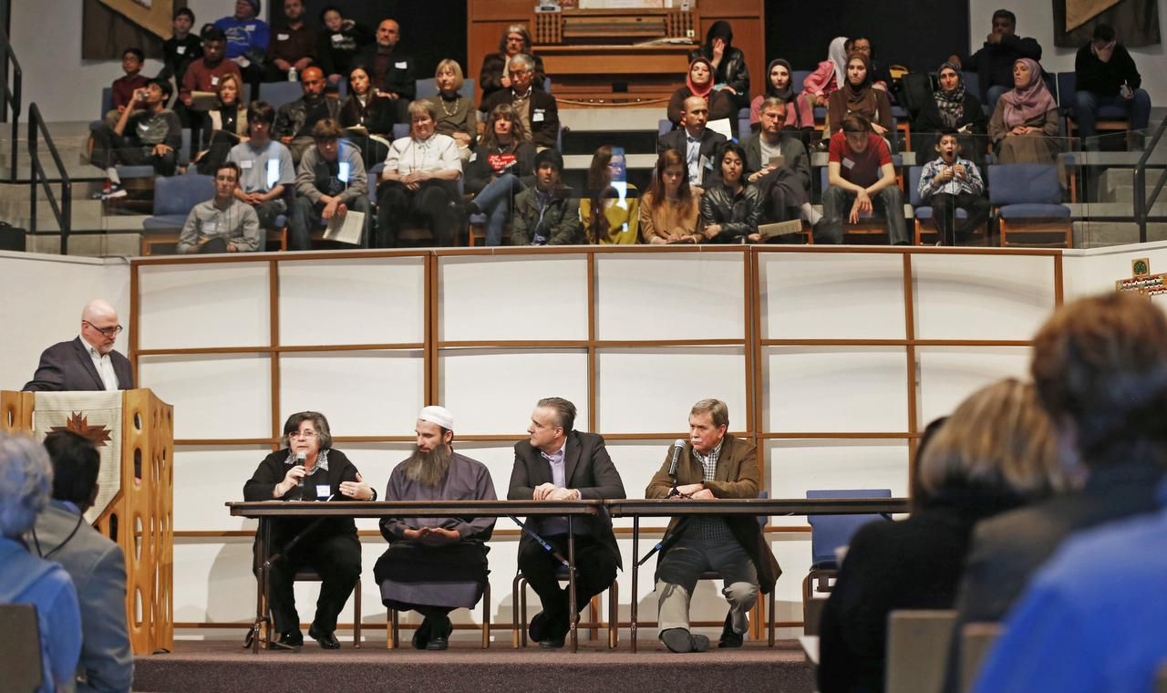 Dr. Hind Jarrah  talked as (from left) Eric Folkerth, Shpendim Nadzaku, Wes Magruder and Lon Burnham listened during Sunday's interfaith Stand With Our Muslim Neighbors gathering at Northaven United Methodist Church.