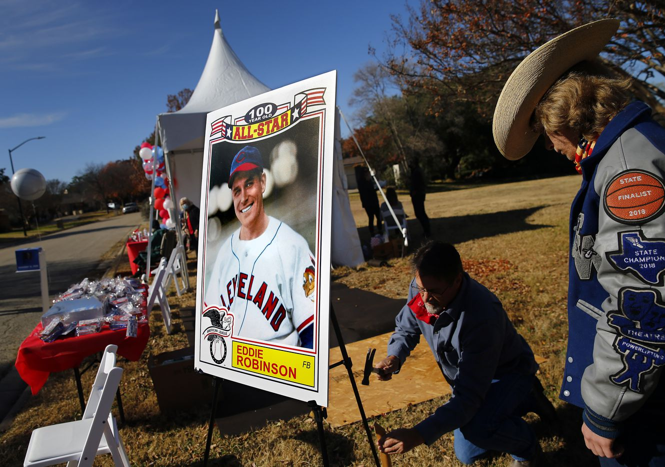 Drew Robinson (center) and his step son Preston Goff anchor a large baseball card of Eddie Robinson, the oldest living former MLB player, who will turn 100 on December 15th. To share his birthday with friends, his family orchestrated a drive-by birthday celebration outside Fort Worth home, Saturday, December 12, 2020. His 65 year career started playing for Cleveland Indians and serving in World War II. Later he went on to play for several other teams before presiding over three winning seasons as Rangers general manager. He is still in great physical health as he waves to passersby, including former teammates, GM Tom Grieve and U.S. congressman and neighbor Marc Veasey. (Tom Fox/The Dallas Morning News)