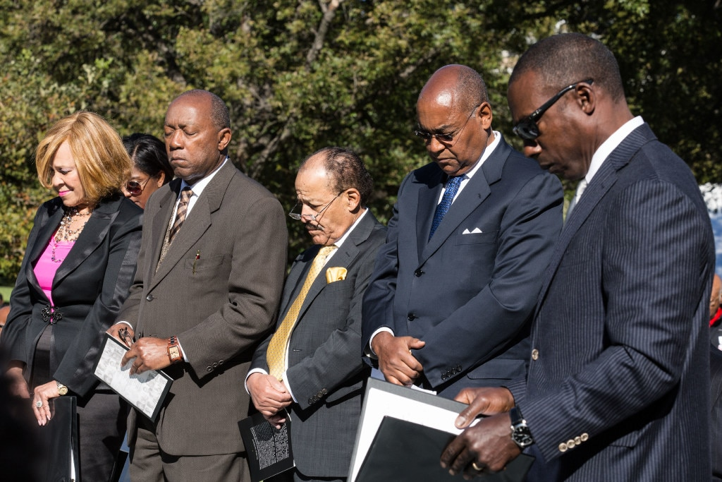 Members of the Texas Legislative Black Caucus, and the Texas African American History Memorial Foundation, bow their heads in prayer Saturday in Austin