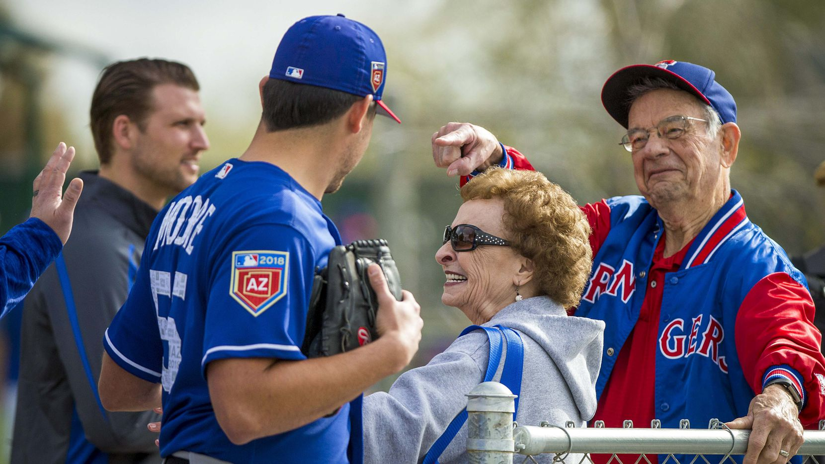 Fans Shirley Kost (center) and her husband Cal Kost (right) wave to Texas Rangers starting pitcher Matt Moore as he takes the field for the first spring training workout for pitchers and catchers at the team's training facility on Thursday, Feb. 15, 2018, in Surprise, Ariz.