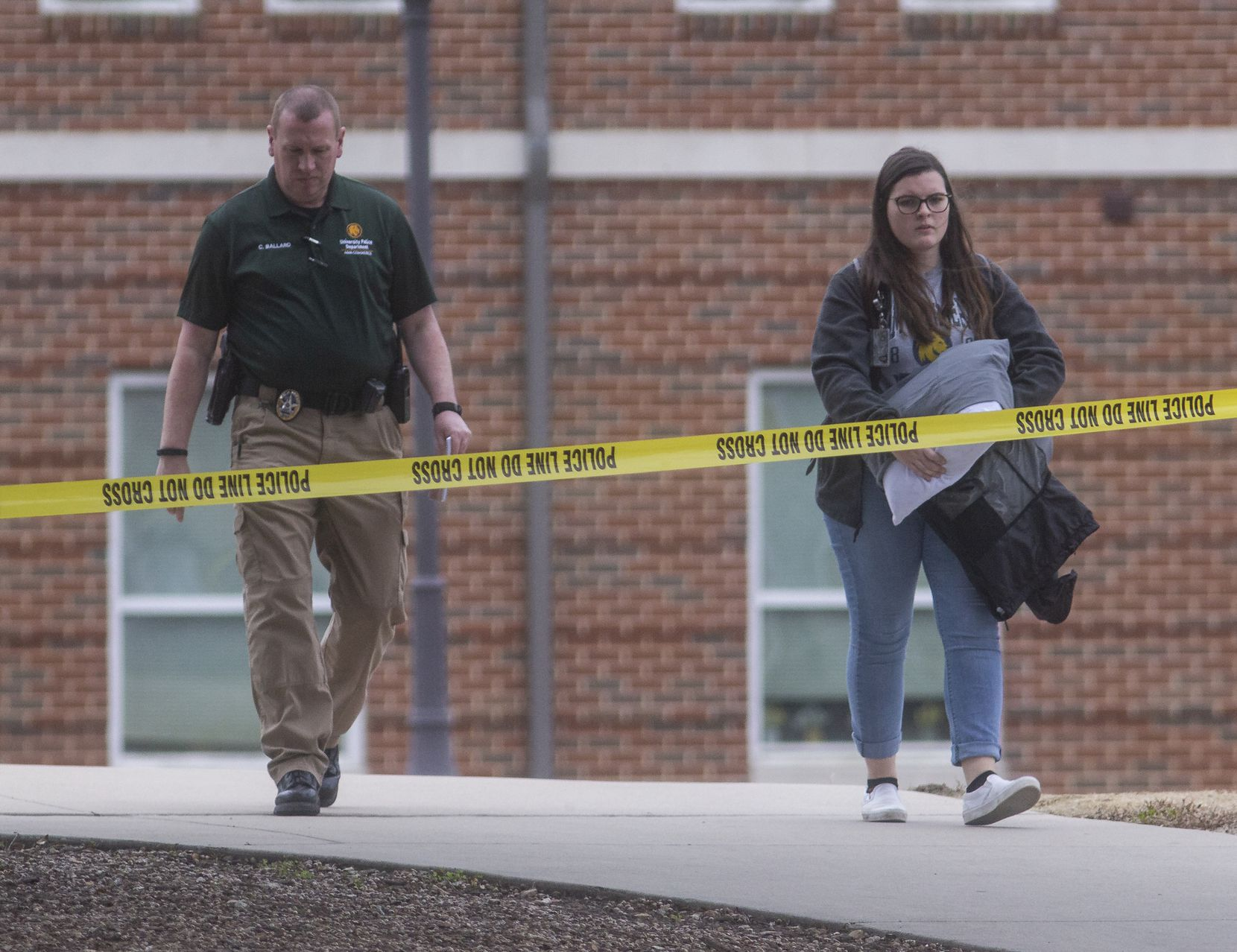 A resident is escorted out of the Pride Rock residence hall where two women were fatally shot and a toddler was wounded Monday at Texas A&M University-Commerce on Feb. 3, 2020 in Commerce, Texas.