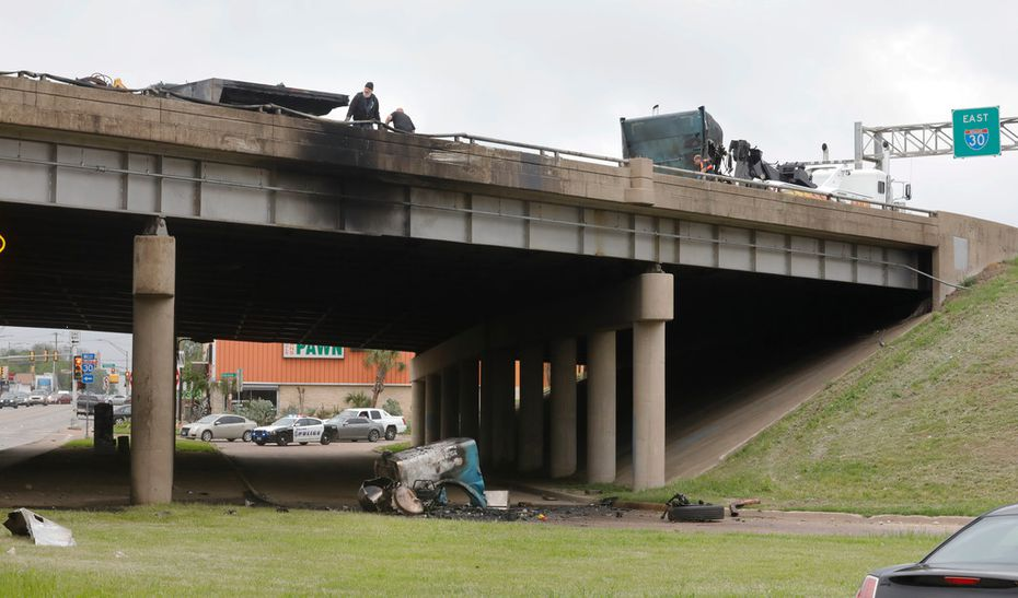 An 18-wheeler exploded and its driver died after an accident at Interstate 30 and East Grand Avenue in Dallas left the rig dangling over a bridge early Friday.