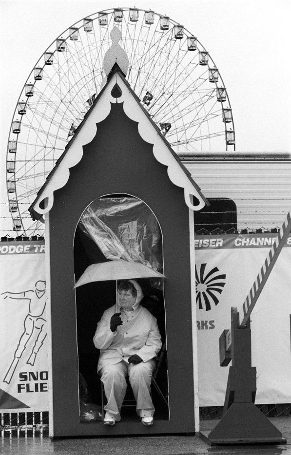 Lift gate operator Peggy Oldham sits in her gate house with her rain suit and umbrella to guard against the rain and wind Saturday morning at the State Fair in 1994. She said she has been working at the State Fair on and off for about 10 years.