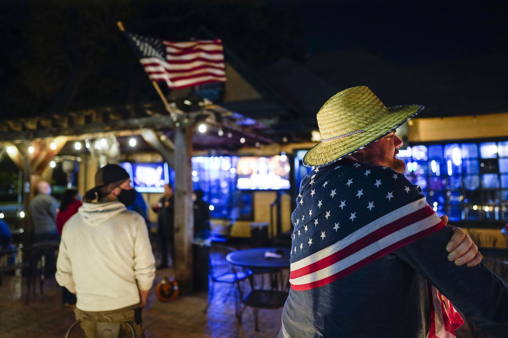 Elliot Fischer (right) wears a flag scarf as he joins others watching election results at Uptown Pub on McKinney on Election Day, Tuesday, Nov. 3, 2020, in Dallas. (Smiley N. Pool/The Dallas Morning News)