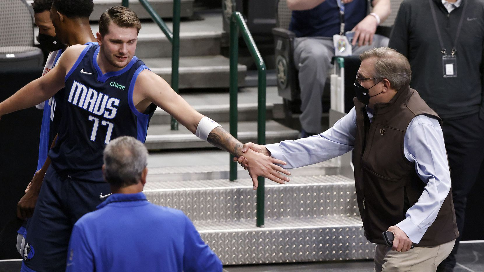 Dallas Mavericks guard Luka Doncic (77) reaches back for General Manager Donnie Nelson as they leave the floor with a lead at the half over the Cleveland Cavaliers at the American Airlines Center in Dallas, Friday, May 7, 2021.