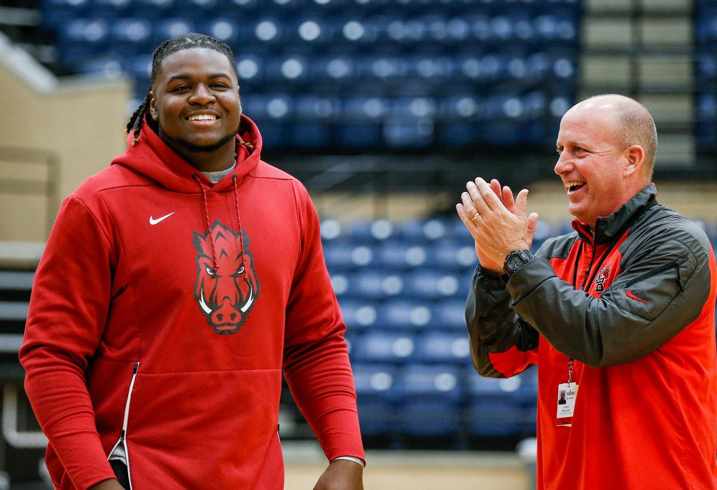 Mansfield Legacy football coach Chris Melson (right) congratulates senior defensive tackle Taurean Carter on signing with Arkansas on national signing day in 2018. (Brandon Wade/Special Contributor)