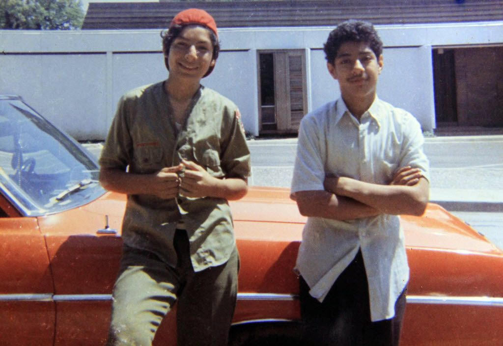 David Rodriguez, 13, left, and his brother Santos Rodriguez, 12, stand by a relative's car in 1973 just one month before Santos was killed by a bullet to the brain fired by a Dallas police officer. The boy died in the police car's front seat during an interrogation in the old Little Mexico neighborhood of Dallas.