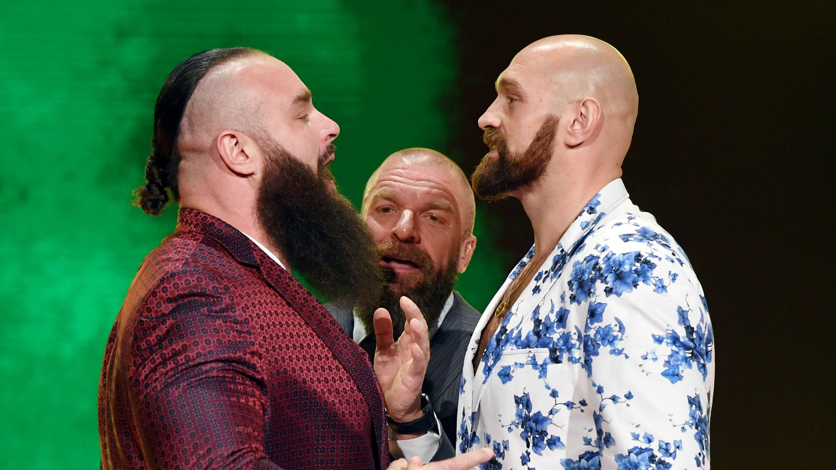 """LAS VEGAS, NEVADA - OCTOBER 11:  WWE Executive Vice President of Talent, Live Events and Creative Paul """"Triple H"""" Levesque (C) gets between WWE wrestler Braun Strowman (L) and heavyweight boxer Tyson Fury (R) as they face off during the announcement of their match at a WWE news conference at T-Mobile Arena on October 11, 2019 in Las Vegas, Nevada."""