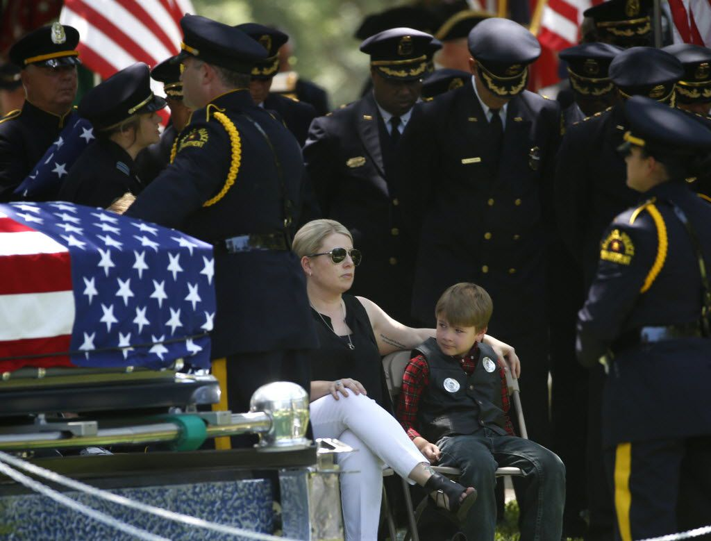 Katrina Ahrens, wife of fallen Dallas police officer Lorne Ahrens, sits with son Magnus Ahrens, 8, at the burial for her husband in the Garden of Honor at Restland Funeral Home and Cemetery in Dallas on July 13, 2016. Ahrens and four other officers were gunned down during an ambush in downtown Dallas.