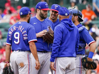 Texas Rangers pitcher Lance Lynn talks with infielder Isiah Kiner-Falefa (9), first baseman Ronald Guzman, catcher Jeff Mathis and manager Chris Woodward as he is lifted from the game during the third inning of a spring training game against the Los Angeles Angels at Tempe Diablo Stadium on Friday, Feb. 28, 2020, in Tempe, Ariz.