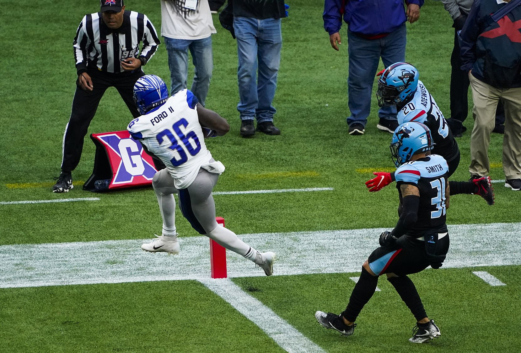 St. Louis Battlehawks running back Keith Ford (36) scores on a 16-yard touchdown run past Dallas Renegades safety Derron Smith (31) and safety Tenny Adewusi (20) during the first half of an XFL football game at Globe Life Park on Sunday, Feb. 9, 2020, in Arlington.