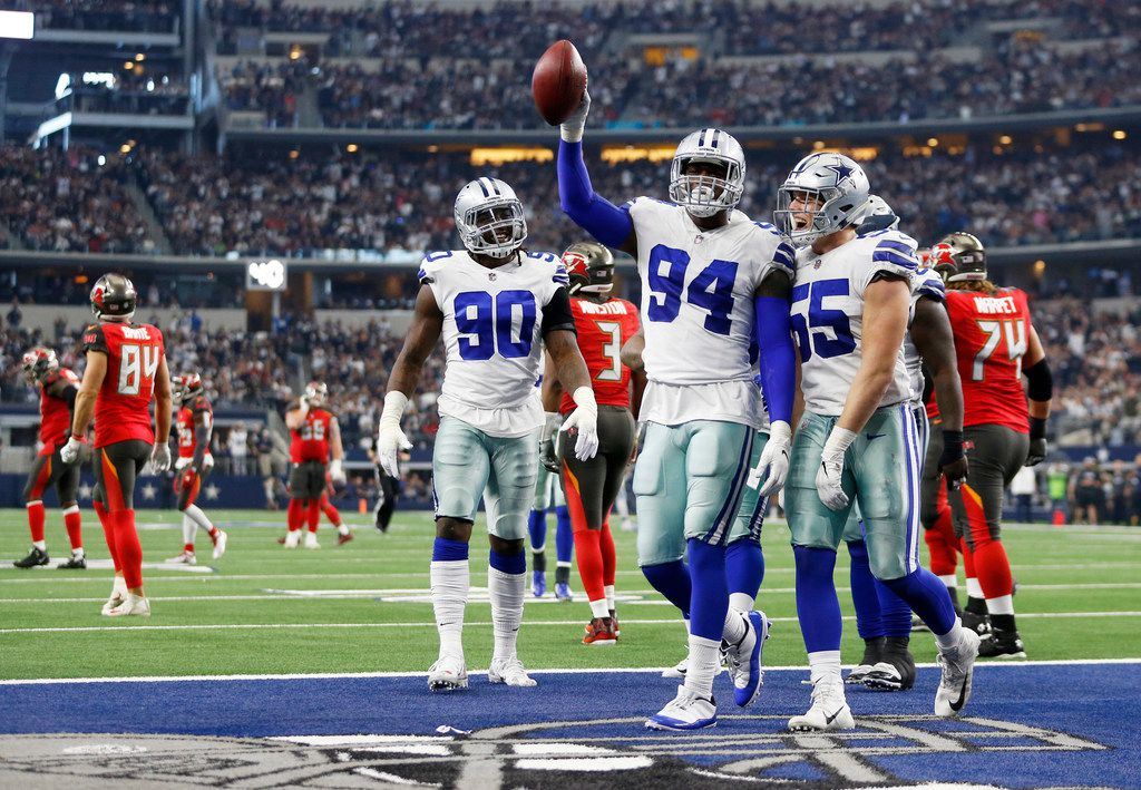 Dallas Cowboys defensive end Demarcus Lawrence (90), and Dallas Cowboys outside linebacker Leighton Vander Esch (55) celebrate with Dallas Cowboys defensive end Randy Gregory (94) after he recovered a fumbled ball from Tampa Bay Buccaneers quarterback Jameis Winston (3) during the second half of play at AT&T Stadium in Arlington, Texas on Sunday, December 23, 2018. Dallas Cowboys defeated the Tampa Bay Buccaneers 27-20 to capture the NFC East. (Vernon Bryant/The Dallas Morning News)